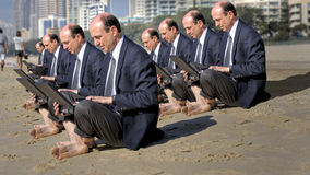 Mobile office. A picture of businessmen (cloned), sitting on a beach and working on their laptop computers Royalty Free Stock Photos