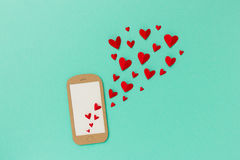 Mobile / Online dating concept with smartphone and hearts Royalty Free Stock Photo