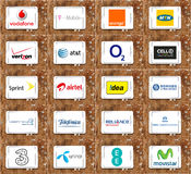 Mobile operator logos and brands. Logos and brands of famous mobile operators in the world on white tablet on rusted wooden background. brands like vodafone , t Royalty Free Stock Photography