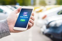 Mobile parking app on smartphone screen. Man holding smart phone with car park application in hand. Internet payment online with modern device. Row of vehicles royalty free stock image