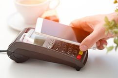 Mobile payment in cafe with smart phone. Nfc near field communication wireless technology royalty free stock images