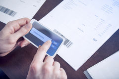 Mobile payment. Man paying bills with mobile phone scanning barcode Royalty Free Stock Image