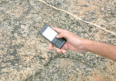 Mobile phone. Image of mobile phone behind the rock pattern Royalty Free Stock Photo
