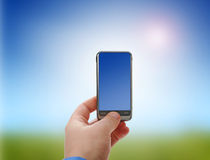 Mobile phone. Mobile phone in hand over sky background Royalty Free Stock Photo