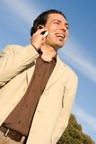 On the mobile phone. Young man with mobile phone laughing Royalty Free Stock Photo