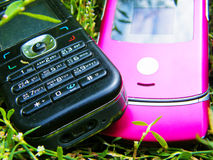 Mobile phone. Pink and black mobile phone on a background of a grass Stock Image
