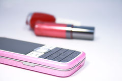 Mobile phone. Womanish  mobile phone and  lipstick and  nail polish Royalty Free Stock Photos