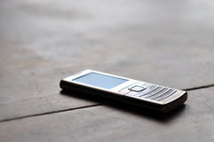 Mobile phone. Metal mobile phone on the old wooden table Stock Photography