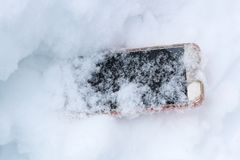 Mobile phone accidentally fell out and got lost in the snow.  stock photos