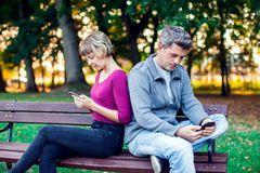 Mobile phone addiction concept - couple looking at their mobile stock images