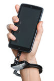 Mobile phone addiction concept. Smartphone and handcuff in hand Stock Photos
