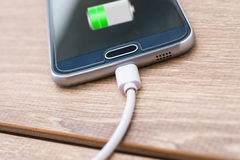 Mobile Phone And Battery Charger Cable On Office Desk Royalty Free Stock Photos