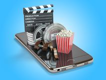 Mobile phone application for creating, seeing end editing video. Files and buying cinema tickets online. Smartphone with film reels, pop corn and clapperboard Royalty Free Stock Photo