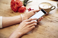 Mobile phone in beautiful woman hands. Lady using internet in cafe. Red roses flowers behind on wooden table. St. Valentine`s day Royalty Free Stock Photos