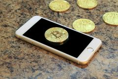 Mobile phone with bitcoin cryptocurrency coins Royalty Free Stock Photography