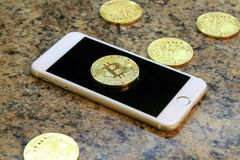 mobile phone with bitcoin cryptocurrency coins on the granite ta Royalty Free Stock Photos