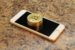 Mobile phone with bitcoin cryptocurrency coins on the granite ta Stock Photography