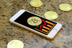 mobile phone with bitcoin cryptocurrency coins on granite ta Stock Photography