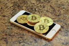 Mobile phone with bitcoin cryptocurrency coins. On the granite table Royalty Free Stock Photos