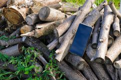 Mobile phone black color is located on a pile of cut branches in the open air Stock Photography