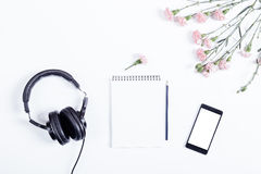 Mobile phone, black headphones, notebook, pencil and flowers lie Stock Photography