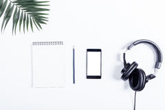 Mobile phone, black headphones, notebook, pencil and green leave Stock Photography