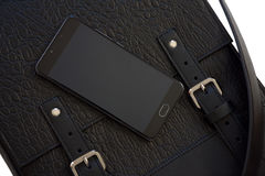 Mobile phone on leather bag. Mobile phone on the black leather bag stock images