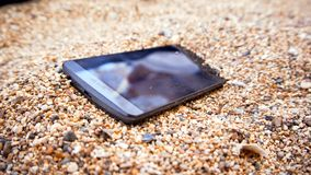 A mobile phone in the sand. A mobile phone with blank black screen sits in the sand at the beach stock images