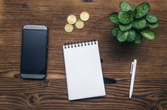 Mobile phone with blank screen. Business ideas concept. Mobile phone with blank screen, notepad with copy space and green plant tree on office desk table top Royalty Free Stock Image