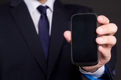 Mobile phone with blank screen in business man hand Royalty Free Stock Images