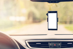 Mobile phone with blank screen in car windshield holder Stock Images