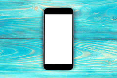 Mobile phone with blank screen mock up isolated on blue wood table background. Smartphone on wood table. Smartfone white screen Royalty Free Stock Photography