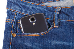 Mobile phone and blue jeans Stock Photos