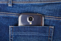 Mobile phone and blue jeans Stock Photography