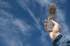 Mobile phone, with blue of sky l. A hand that catches a mobil phone, with blue of the sky in deep Royalty Free Stock Photos