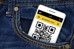 Mobile phone with boarding pass in jeans pocket Stock Photo
