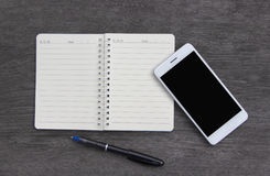 Mobile phone and book note on  wooden desk Stock Images