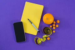Mobile phone, book, pen, measuring tape and citrus fruit Stock Images