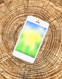 Mobile phone with bright screen on wooden cracked background Royalty Free Stock Photos