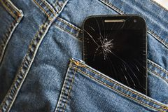 Mobile phone broken cracked touch screen in the back pocket of jeans denim trousers in accident and careless concept. Mobile phone broken and cracked touch Stock Photo