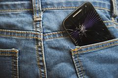 Mobile phone broken cracked touch screen in the back pocket of jeans denim trousers in accident and careless concept. Mobile phone broken and cracked touch Royalty Free Stock Photos