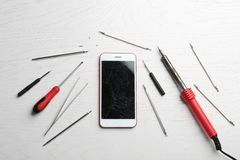 Mobile phone with broken display and repair tools on wooden table royalty free stock images