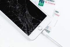 Mobile phone with broken display and Russian money on white background. Mobile phone with broken display and Russian money to pay for repairs on a white royalty free stock photo