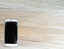 Mobile phone with broken screen and empty background. White smartphone with broken screen and empty background royalty free stock image