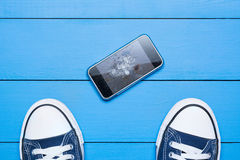 Mobile phone with broken screen on floor. Concept stock images