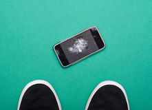 Mobile phone with broken screen on floor. Mobile phone with broken screen on green floor royalty free stock photography