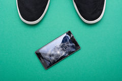 Mobile phone with broken screen on floor. Mobile phone with broken screen on green floor stock image