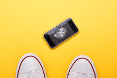 Mobile phone with broken screen on floor. Mobile phone with broken screen on yellow floor royalty free stock photos