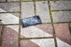 Mobile phone with broken screen on a pavement. royalty free stock photo