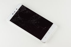 Mobile phone with broken screen. White mobile phone with a broken screen royalty free stock photo
